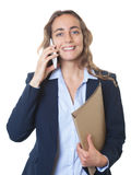 Blond businesswoman with blue eyes and blazer at phone Stock Photos