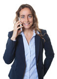 Blond businesswoman with blue eyes and blazer talking at phone Royalty Free Stock Images