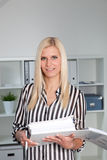 Blond Businesswoman Casually Dressed in Office. Portrait of Blond Businesswoman Casually Dressed in Striped Shirt Holding Open Binder in Office Stock Photo