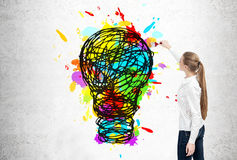 Blond businesswoman drawing light bulb Royalty Free Stock Images