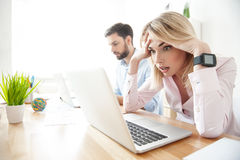 Blond businesswoman has problems with work. Young women is looking at laptop with shock. She is touching head and opening mouth with disappointment. Man is Royalty Free Stock Photography