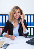 Blond businesswoman at office at phone laughing at camera Royalty Free Stock Image