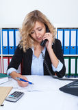 Blond businesswoman at office at phone writing note Stock Photo