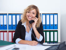 Blond businesswoman at office speaking with client at phone. With documents on the desk Stock Photo