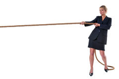 Blond businesswoman pulling on rope. A blond businesswoman pulling on a long piece of rope, isolated on a white background Stock Photos