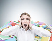 Blond businesswoman screaming, piles of books Royalty Free Stock Photos