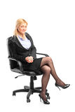 Blond businesswoman sitting in an office chair Royalty Free Stock Images