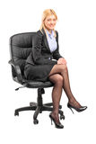 Blond businesswoman sitting in an office chair Stock Images