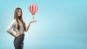 A blond businesswoman stands and holds one hand palm up with small red and white hot air balloon above it. Stock Photo