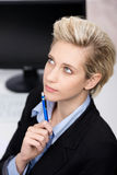 Blond Businesswoman Thinking At Office Desk Royalty Free Stock Photos
