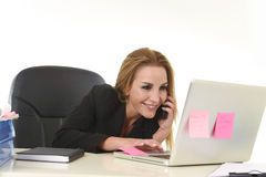 Blond businesswoman working at office laptop computer desk talking on mobile phone smiling Stock Photography