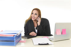 Blond businesswoman working at office laptop computer desk talking on mobile phone smiling Royalty Free Stock Photo