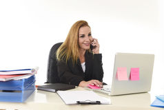 Blond businesswoman working at office laptop computer desk talking on mobile phone smiling Stock Images