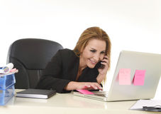 Blond businesswoman working at office laptop computer desk talking on mobile phone smiling Royalty Free Stock Image