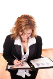 Blond businesswoman writing on documents Royalty Free Stock Photography