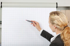 Blond Businesswoman Writing At Flip Chart In Office. Portrait of young blond businesswoman writing at flip chart in office Stock Images