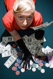 Blond with cash on the poker table royalty free stock photography