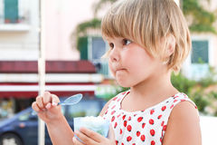 Blond Caucasian baby girl eats frozen yogurt Stock Images