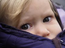 Blond caucasian baby girl with gray eyes in winter jacket lookin stock photo