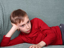 Charming blond Caucasian boy in red lying on green sofa thinking. Blond Caucasian boy in read sweater lying on green sofa thinking and relaxing watching away Stock Image