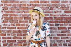 Blond Caucasian Girl Licks Ice Cream Against a Brick Wall Cone Fedora Hat. Pretty young white girl licks an ice cream cone with a fedora hat in the summer stock photos