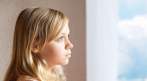 Blond Caucasian girl near window with blue sky Royalty Free Stock Photography