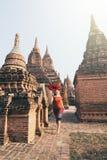 Blond Caucasian kvinna med röda paraplykörningar bland tempel och pagoder av forntida Bagan i Myanmar royaltyfria bilder