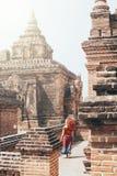 Blond Caucasian kvinna med röda paraplyställningar bland tempel och pagoder av forntida Bagan i Myanmar fotografering för bildbyråer