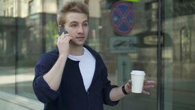 Young man with coffee walking along building and talking on phone stock video