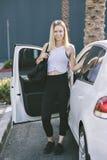 Blond Caucasian Millennial kvinnlig med idrottshallpåsen och genomkörarekläder som går ut hennes bil arkivfoton