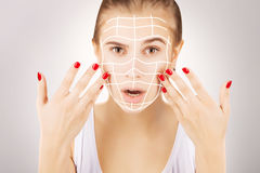Blond caucasian model portrait with surgery lines on face, grey Royalty Free Stock Photography