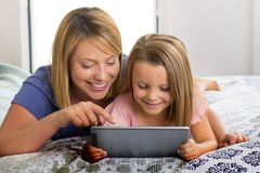 Blond Caucasian mother lying on bed with her young sweet 7 years old daughter using internet on digital internet tablet pad togeth stock photos