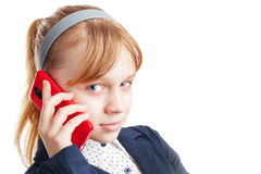Blond Caucasian schoolgirl calling by mobile phone. Portrait iso Stock Photography