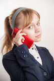 Blond Caucasian schoolgirl calling by mobile phone Royalty Free Stock Image