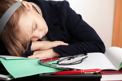 Blond Caucasian schoolgirl sleeps on the desk Stock Images