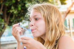 Blond Caucasian teenage girl eats frozen yogurt Royalty Free Stock Images