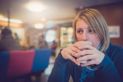 Blond woman drinking hot coffee stock images