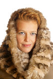 Blond caucasian woman with ecologic fur hood. Portrait of a caucasian blond woman with blue eyes wearing an ecologic fur hood over a white background Royalty Free Stock Image