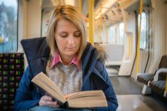 Woman reading book in a train Royalty Free Stock Photos