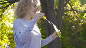 Blond caucasian woman staying in the sunrays and blowing soap bubbles. Happy smiling girl enjoying last warm days. Outdoors stock video footage