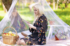 Blond Caucasian Woman Using Ebook Tablet Reader Outside in Fores Royalty Free Stock Images