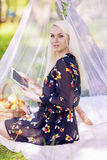 Blond Caucasian Woman Using Ebook Tablet Reader Outside in Fores Stock Photos