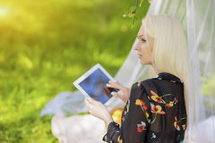 Blond Caucasian Woman Using Ebook Tablet Reader Outside in Fores Royalty Free Stock Photos