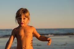 Blond caucasien petite fille sur le sable de plage au coucher du soleil photographie stock libre de droits