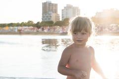 Blond caucasien petite fille sur le sable de plage au coucher du soleil photos libres de droits