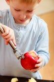 Blond chłopiec dziecka dzieciaka preschooler obierań owocowy jabłko w domu Fotografia Stock