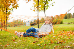 Blond chłopiec kłaść na sieci hamak w parku Fotografia Royalty Free