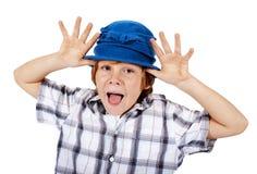 Blond chłopiec z błękitnym kapeluszem robi twarzom Obrazy Stock