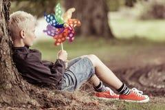 Blond chłopiec trzyma kolorowego whirligig siedzi drzewem Zdjęcie Stock