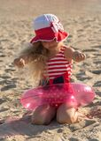 Blond girl in lifebuoy ring on the sand. Blond charming girl in lifebuoy ring on the bright beautiful sand Royalty Free Stock Images